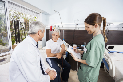 Happy senior patient looking at doctor while nurse holding reports in rehabilitation center